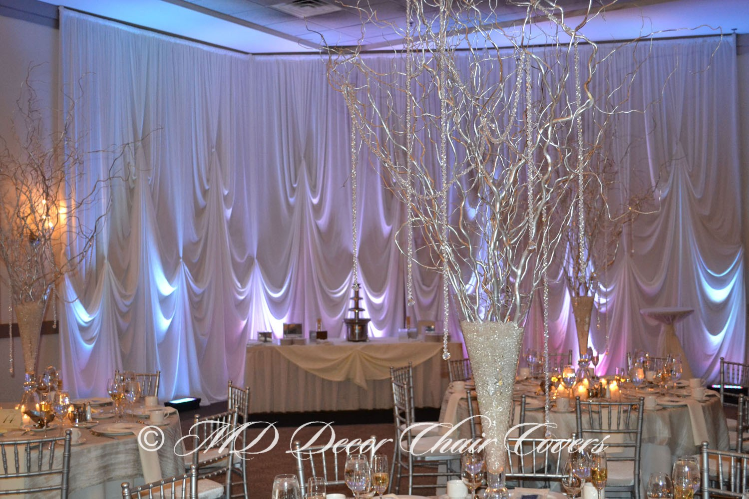 Silver chiavari chairs with a multiple light back drop